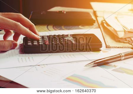 Close Up Woman Using Calculator In Home Office.