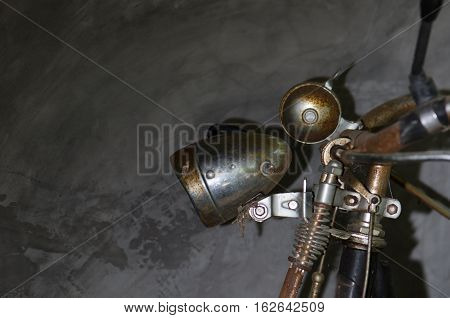 The old bike was parked cement wall left home. Rusty old lamp And bell on the handlebars.