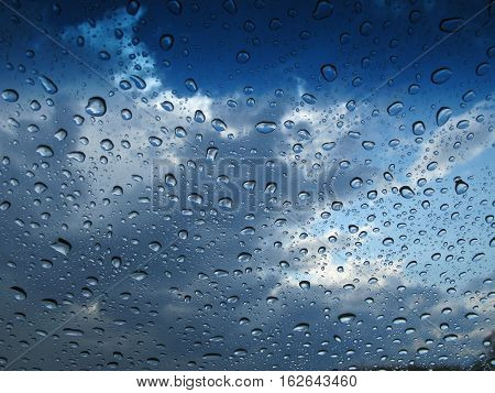 Seen through a window on which raindrops glisten is a sky filled with clouds of various hues of blue.