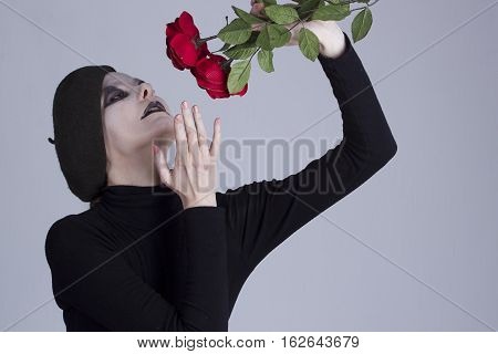 Young beautiful woman mime with red roses