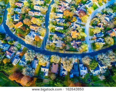 Aerial View Over Modern Suburb Home Community neighborhood with colorful Fall Autumn trees around curved streets and new development outside of Austin , Texas looking straight down