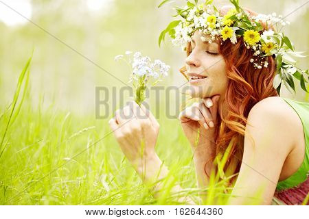 Young beautiful girl in wreath enjoying scent of wildflowers