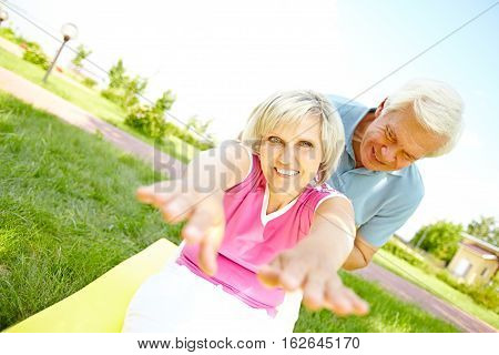 Senior woman stretching with her husband s assistance