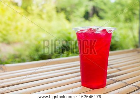 Soft drinks in plastic cups on bamboo table
