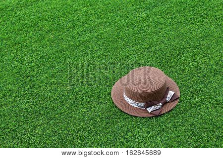 Brown ladies hat on turf texture background with copy space.