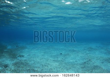 Shallow underwater sea floor void of fish or reef life with vanishing visibility into deep blue darkness at Cozumel Mexico