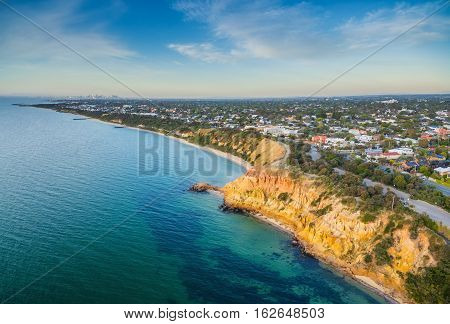 Aerial Panorama Of Black Rock Suburban Area And Colorfoll Cliffs Of The Coastline At Sunset.