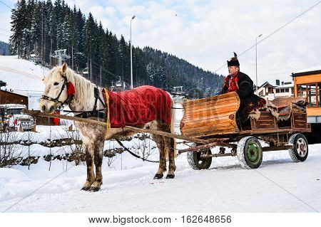 BUKOVEL, UKRAINE - December 17, 2016: Wooden cart with white horse and man in ukrainian national suite of ski resort Bukovel, Ukraine. Bukovel is the most popular ski resort in Ukraine.Carpathian.
