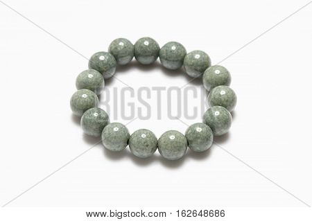 Lucky green stone bracelet on white background.