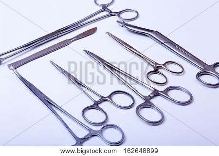 surgical instruments and tools including scalpels forceps and tweezers arranged on a table for a surgery.