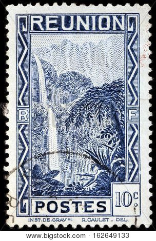 LUGA RUSSIA - NOVEMBER 06 2016: A stamp printed by REUNION shows beautiful view of the Salazie Waterfall. Reunion is an island and region of France in the Indian Ocean circa 1933.