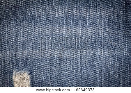 Denim jeans texture or denim jeans background with old torn. Old grunge vintage denim jeans. Stitched texture denim jeans background of jeans fashion design. Dark edged.