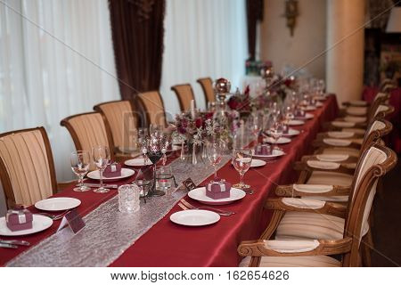 restaraunt tables with red tablecloth, red wedding decor, table of newly married