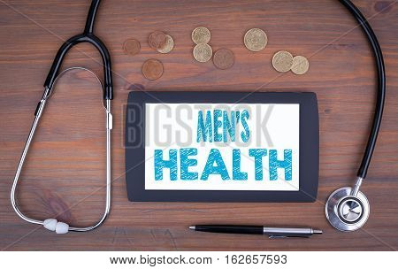 Men's Health. Text on tablet device on a wooden table