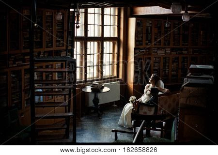 Couple Looks Out The Window In The Old Library
