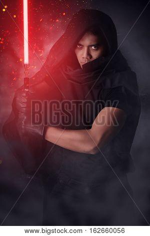 Dark warrior holding a light saber over a dark background