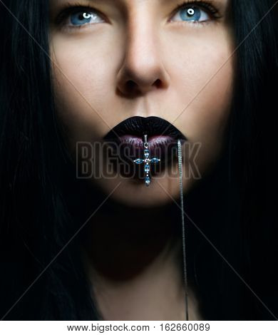 Portrait of dark hair woman with dark lips with cross in her mouth