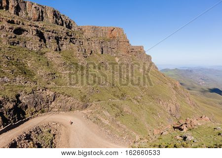 Mountains  hiker hiking walking up steep mountain dirt road pass landscape