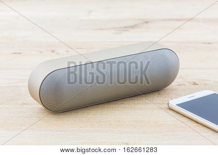 Wireless speaker for mobile phone Speaker for smartphone on wood desk Background.