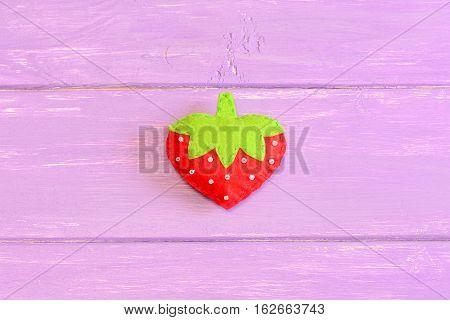 How to hand sew a children toy strawberry. Step. Tutorial. Kids felt toy strawberry isolated on purple wooden background. Easy kids sewing instruction. Top view