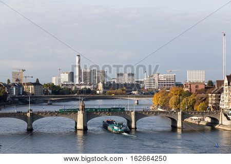 Basel, Switzerland - October 24, 2016: Container ship on the Rhine river passing under Middle Bridge in the city center