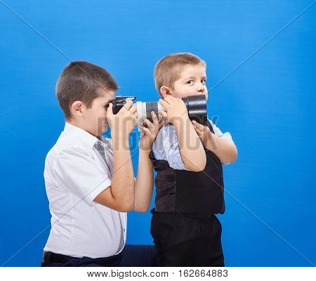 The younger brother helps older brother photograph