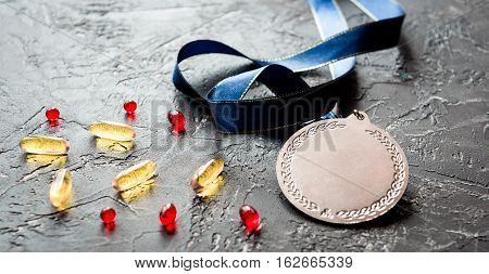 Concept of doping in sport - deprivation medals close up on dark background