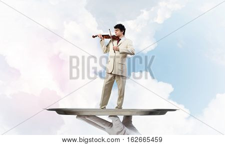 Hand of waiter presenting on tray man playing violin