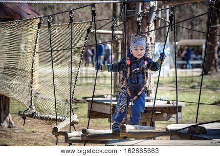 Kiev, Ukraine - March 30, 2016: A Kid Crossing A Rope Bridge At