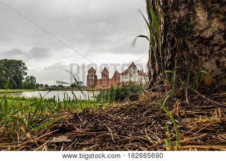 Mir, Belarus - September 05, 2016:  View of medieval castle in the Belarusian town of Mir through the trees against the somber sky. Mir Castle Complex