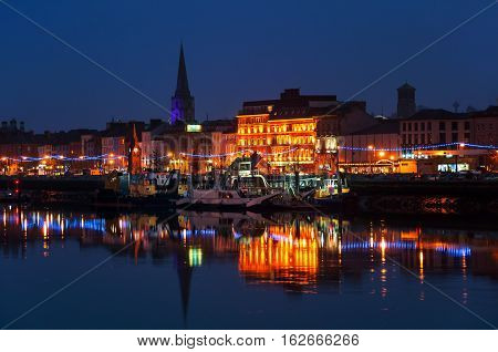 Waterford Ireland. Panoramic view of a cityscape at night with illumination in Waterford Ireland. It is the oldest city in the country where located many restaurants shops bars. Moored ship.