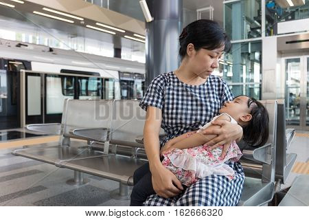 Asian Chinese Mother Carrying Sleeping Daughter Inside A Mrt Station