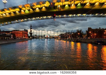 Boat ride at night in Moscow Russia. Famous landmarks illuminated Kremlin. Sunset cloudy sky in Moscow the capital of Russia. Motion blurred bridge over Moscow river