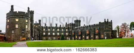 Kilkenny Castle during the day. It is one of the most visited tourist sites in Kilkenny Ireland. Castle grounds with green lawn and flowers. Landmark in small town of Ireland