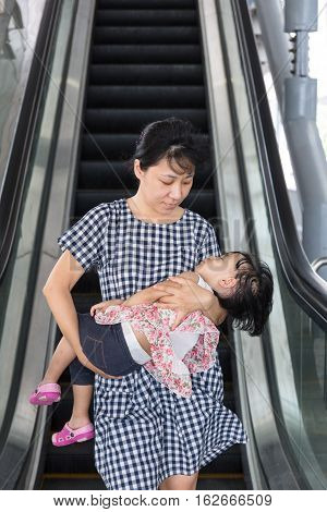 Asian Chinese Mother Carrying Sleeping Daughter Taking Escalator At Mrt