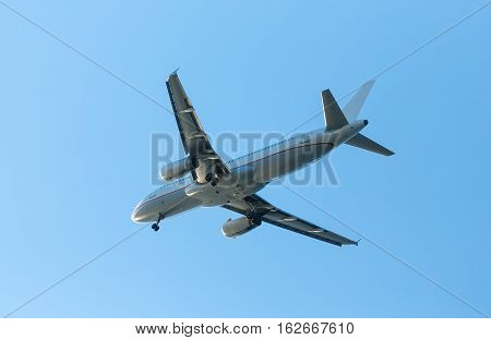 A white airplane flying in a clear pale blue sky.