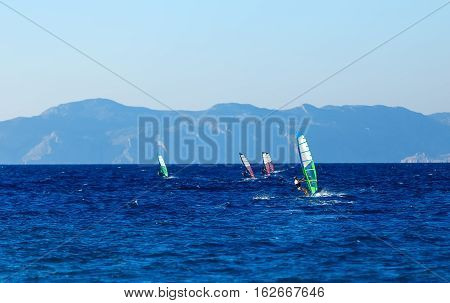 group of windsurfers on a background of mountains in the Aegean sea .