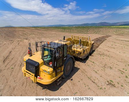 Modern vehicle cultivating ground in the summer time