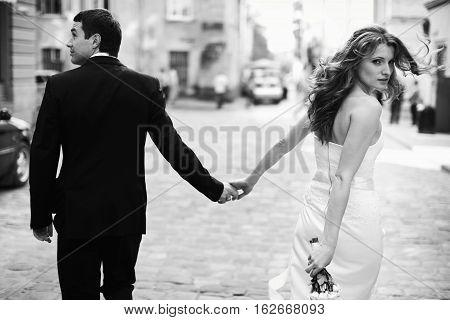 Bride Turns Around Holding Groom's Hand While Walking Around The City