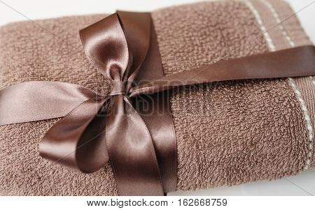 Brown towel tied with a brown bow on white
