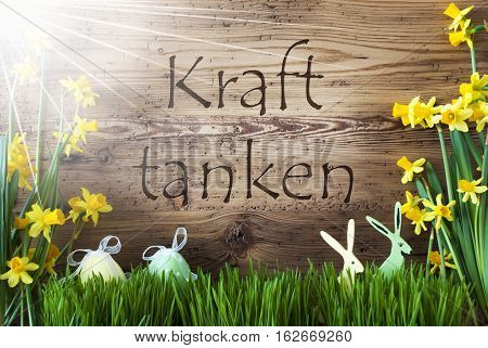 Wooden Background With German Text Kraft Tanken Means Relax. Easter Decoration Like Easter Eggs And Easter Bunny. Sunny Yellow Spring Flower Narcisssus With Gras. Card For Seasons Greetings