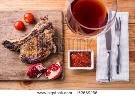 Rib eye steak on chopping board with silverware and glass of red wine