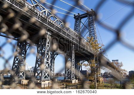 Abstract view through fence of Williamsburg Bridge towards Brooklyn in New York City