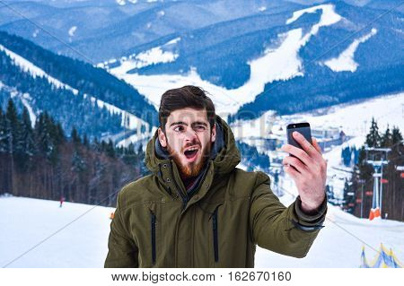 Front view of emotional male brunet man with beard wearing green jacket making self portrait at call phone. Using smart phone against landscape of Carpathian mountains at ski resort Bukovel.