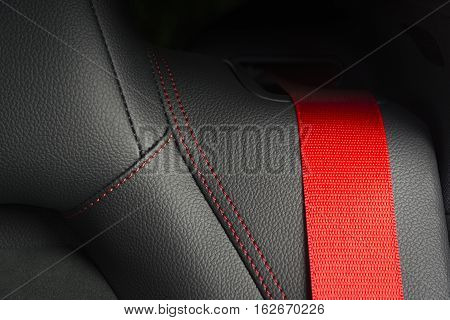Part of sport seat with red safety belt in modern sport car