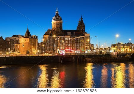 AMSTERDAM, NORTH HOLLAND/THE NETHERLANDS - DECEMBER 4, 2016: View of the city with Church of St.Nicholas and Schreierstoren     at night during Light Festival