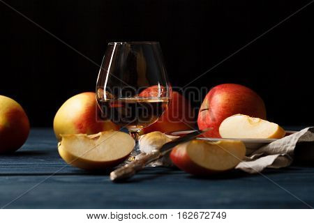 Freshly Squeezed Apple Juice In Glass And Red Apples With Leaves On Old Wood, In Front Of White Back