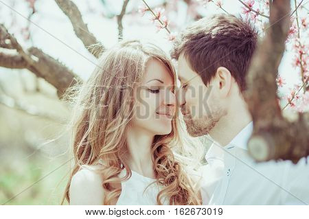 Young happy couple in love outdoors. loving man and woman on a walk in a spring blooming park.