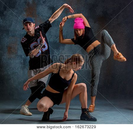 The two young girls and boy dancing hip hop at the blue studio background