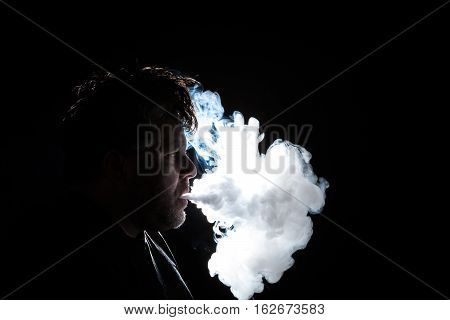 Profile View Of A Man With Vapor Being Blown From His Lips